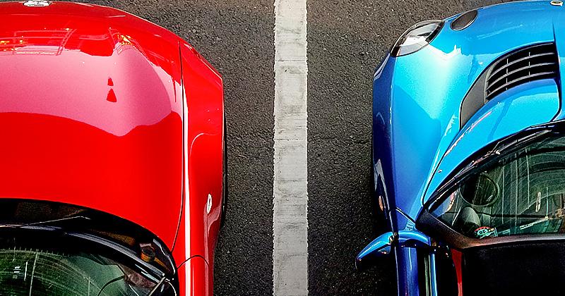 Rotes und blaues Auto auf Parkplatz